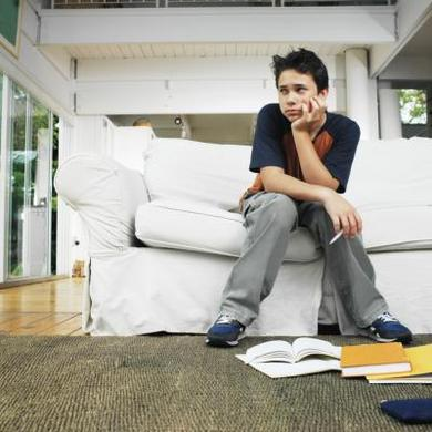 boy unhappy studying on couch